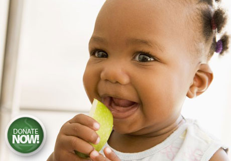 Young black baby eating apple slice - Project Topeka Community Food Drive